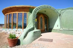 Entrance of an Earthship sustainable house made out of adobe and upcycled glass bottles near Taos in New Mexico, USA. View of the hand-made entrance of an stock images