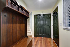 Entrance foyer features pale yellow walls. Built-in closet with dark green doors, wood bench with open shelves filled with wicker storage baskets  and hardwood Royalty Free Stock Photos