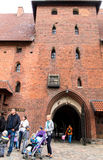 Entrance gate of gothic castle, Malbork. Photo shows group of people standing in front of entrance to Malbork castle, Poland. The castle built in gothic style Stock Image