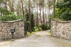 Entrance gate to a rustic, english house in the forest with stone wall and cobblestone driveway stock photography