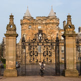 Entrance gates to the Palace of Holyroodhouse in Edinburgh. An eager tourist takes pictures from the closed main gates of the Palace of Holyroodhouse, located at Stock Photography
