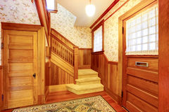 Entrance hallway with staircase and beige carpet covered steps. Entrance hallway with wooden staircase, beige carpet covered steps and plank paneled walls Royalty Free Stock Photo