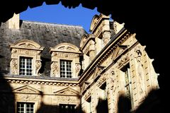 Marais hotel de Sully entrance historical building Paris. The entrance of Hotel de Sully historical building with its adornments, grey roof, chimneys and bas Stock Photography