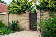 Entrance house group with a wicket and stone fence surrounded by green bushes and trees. Horizontal frame stock photography