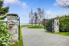 Entrance iron gates with stone columns. View of driveway and roundabout Stock Images
