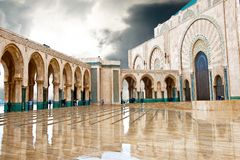Entrance King Hassan II Mosque, Casablanca, reflecting in puddle.