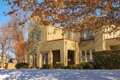 Entrance of landscaped stucco two story house with snow on the ground in upscale neighborhood Stock Photos