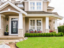 Entrance of a luxury house on a sunny day. Entrance of a luxury house with beautiful landscaping on a bright, sunny day. Home exterior design stock photos