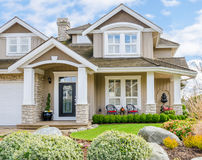 Entrance of a luxury house on a sunny day. Entrance of a luxury house with beautiful landscaping on a bright, sunny day. Home exterior design Royalty Free Stock Photography