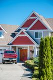 Entrance of luxury residential house with red car parked on the driveway. Red residential house with red truck in front of the. Entrance of luxury residential stock photo