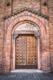 Entrance of a medieval cathedral with wooden door. Royalty Free Stock Photography
