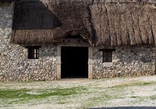 Entrance of an old rural stone building with thatched roof. Entrance of an old rural building with thatched roof  and stone medieval walls Royalty Free Stock Image