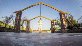 Entrance passageway. An unusual entrance passageway built of four stone pillars supporting girders with a lighthouse in the background Royalty Free Stock Photography