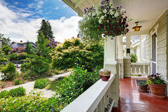 Entrance porch with flower pots overlooking front yard. Entrance porch in old house with flower pots. View of walkway adn front yard landscape Stock Image