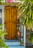 Entrance and porch to Key West House with rustic hurricane shutter by door and rusted bike parked surrounded by tropical greenery stock image