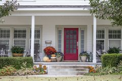 Entrance and porch to pretty house with Autumn and Halloween decorations and fall leaves blowing in the wind - curb appeal.  royalty free stock photography