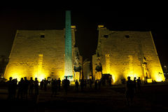 The entrance pylon of the Luxor Temple (Temple of Amun-Ra) in Luxor, Egypt. The enterance is highlighted by the obelisk and two giant statues of Ramesses 2nd Royalty Free Stock Image