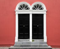 Entrance of Red Building with Stone Steps and Pair of Black Doors with Fan Transoms royalty free stock photo