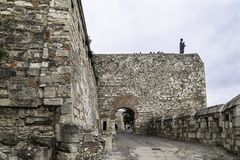 Entrance through the road that climbs to the Buda Castle, with the defensive wall and on top the Statue of the Virgin Mary. Entrance on the road that goes up to stock photos