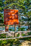 An entrance road going to the seaside in Acadia National Park, Maine. Acadia National Park, ME, USA - August 15, 2018: A welcoming signboard at the entry point royalty free stock photos