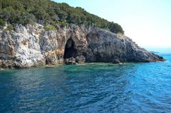 The entrance of a sea cave. Beautiful turquoise water of the sea and a sea cave entrance somewhere in Greece Stock Images