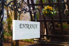Entrance sign made of wood with white color hanging on a black steel beam royalty free stock photo