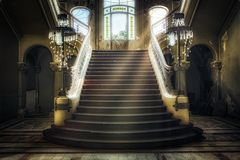 Entrance with symmetrical stairs of an abandoned casino. Sunlight shines through the windows and lights the darkness Stock Photos