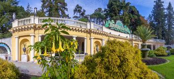 The entrance to the Arboretum in Sochi. Russia. The face of the Arboretum is the entrance with lawn and palm tree. Beautiful building attracts residents and Stock Photo
