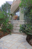 Entrance to beautiful modern home. Stairway lined with shrubbery to entrance of modern home Royalty Free Stock Image