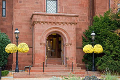 Entrance to brick mansion. A view of the entrance or doorway into a large red brick mansion with bright, colorful hanging mums Royalty Free Stock Image