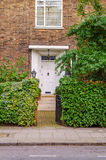 The entrance to a building stone steps on botj sides green veget Stock Photo