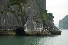 Water laps at a cave at the base of a limestone cliff in Halong Bay. Stock Image