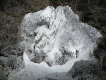 Entrance to a cave covered in snow stock photography