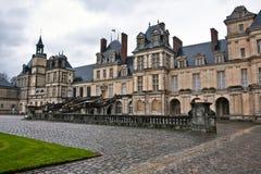 Entrance to the Chateau de Fontainebleau, Paris. Chateau de Fontainebleau on a rainy day, residence of Napoleon I, Paris, France royalty free stock image