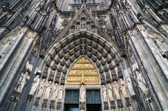 Entrance to Cologne Cathedral. Figures of saints on the facade. Stock Photos