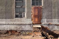 Entrance to destroyed building, wooden door, metal staircase, wi royalty free stock photos