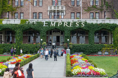 Entrance to The Empress hotel, Victoria, Canada. Tourists on flower lined sidewalk leading to the ivy covered entrance of The Fairmont Empress hotel in Victoria Stock Photo