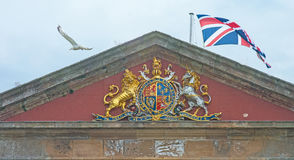 Entrance to Fort George with seagull. Lions rampant at the entrance to Fort George together with the Union Jack flag blowing in the wind and a seagull, pale blue stock photo
