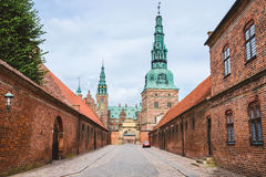 Entrance to Frederiksborg castle in Copenhagen, Denmark - September, 24th, 2015. Red brick fortress wall and green copper spiels. Of towers of renaissance stock photo