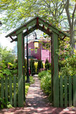 Entrance to the garden. Green wooden fence and an arch at the entrance to the garden stock photo