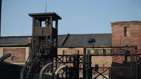 Distant view of a German watchman guarding a concentration camp while standing in a watchtower. WWII reenactment. Entrance to a German death camp with a security stock video footage