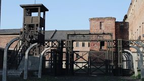 Distant view of a German watchman guarding a concentration camp while standing in a watchtower. WWII reenactment. Entrance to a German death camp with a security stock footage