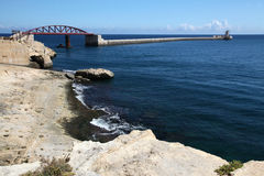 Entrance to Grand harbour, Malta. The impressive breakwater at the entrance to Grand harbour Malta with a new bridge which was installed in 2011 Stock Photo