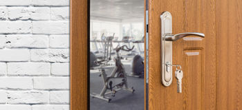 Entrance to gym in fitness club, opened door with exercise bikes Stock Photos