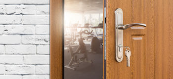 Entrance to gym in fitness club, opened door with exercise bikes Stock Image
