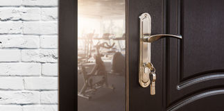 Entrance to gym in fitness club, opened door with exercise bikes Stock Photo