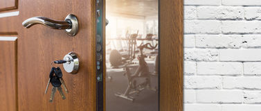 Entrance to gym in fitness club, opened door with exercise bikes Royalty Free Stock Image