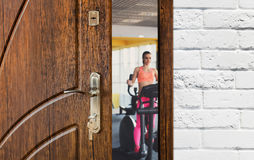 Entrance to gym in fitness club, opened door with woman on elliptical trainer Stock Images