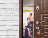 Entrance to gym in fitness club, opened door with woman on elliptical trainer Royalty Free Stock Photos