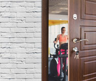 Entrance to gym in fitness club, opened door with woman on elliptical trainer Stock Photography
